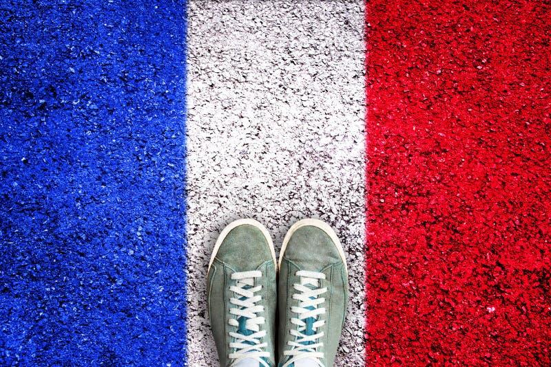 Folâtrez les chaussures sur l'asphalte avec le concept français d'élection de drapeau photo libre de droits