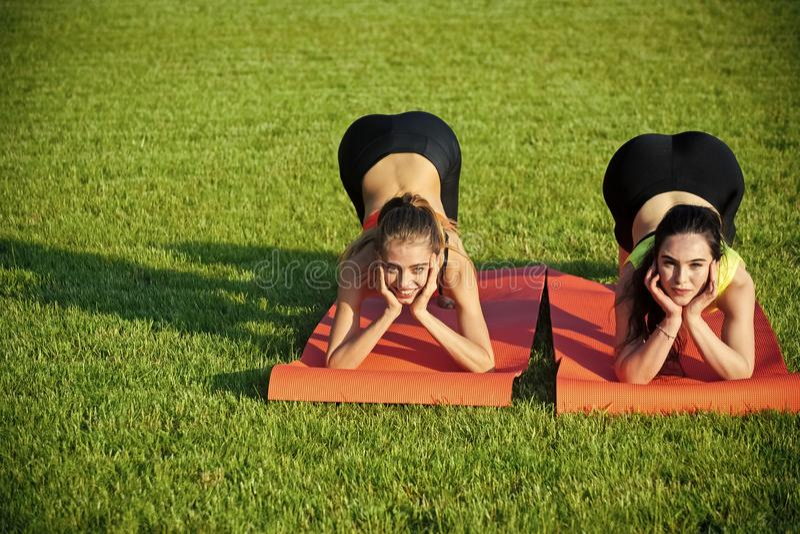 Folâtrez les femmes s'exerçant sur des tapis de yoga sur l'herbe verte image libre de droits