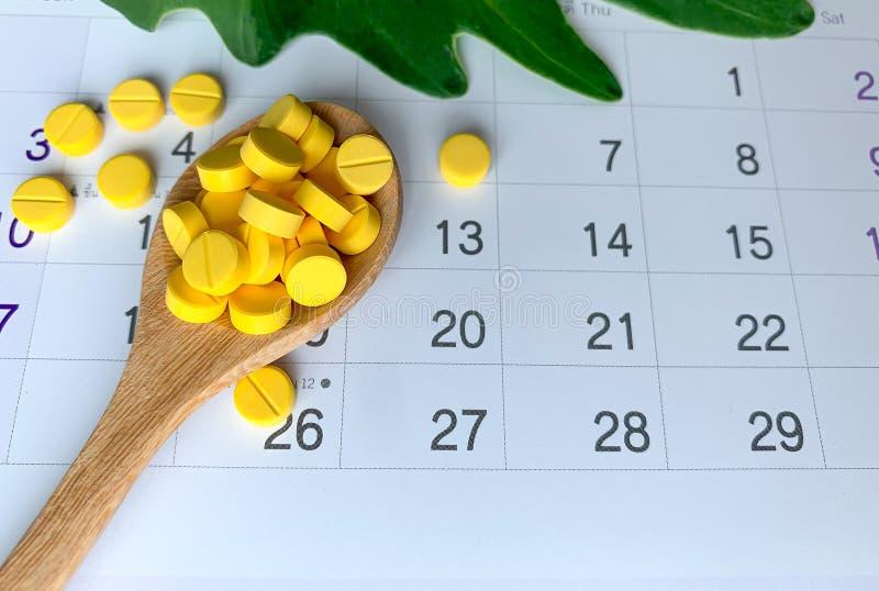 Fol- Tabletten auf einem hölzernen Löffel werden auf den Kalender gesetzt lizenzfreies stockbild