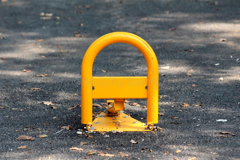 Fold down vehicle security car parking lock safety barrier mounted on paved parking lot surrounded with fallen leaves royalty free stock photo