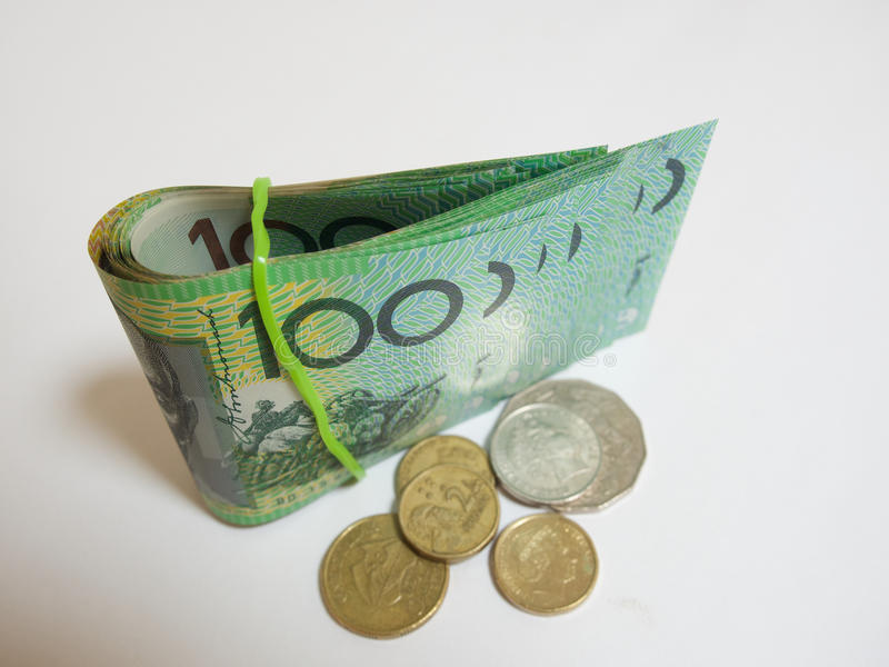 Fold of green Australian $100 dollar notes plus coin. Several hundred dollar Australian bank notes. Some folded with elastic band. and some flat. $100 Australian stock image