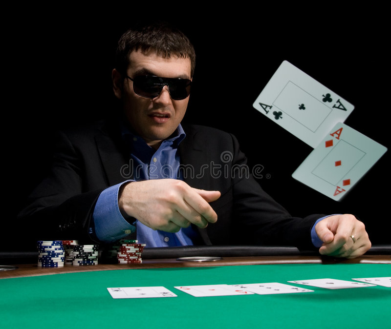 Fold in poker with two aces. Stylish man in black suit folds two aces in casino poker at Las Vegas over black royalty free stock image