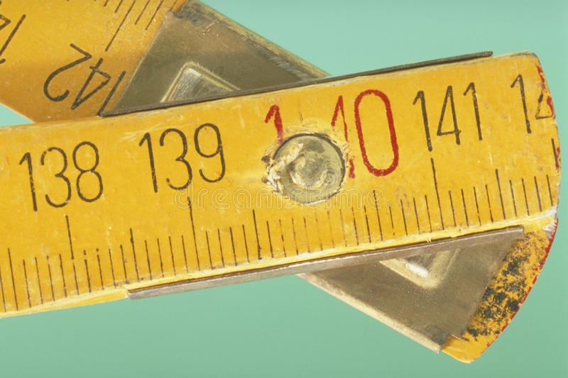 Foldable yellow ruler. The turning point of a foldable yellow ruler in close up royalty free stock photos