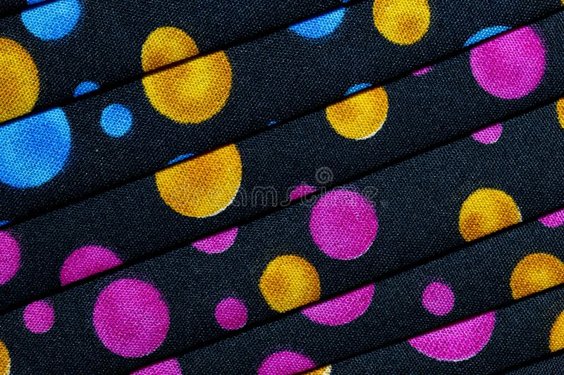 Folded fabric with red, blue, pink, gold and green dots / circles royalty free stock images