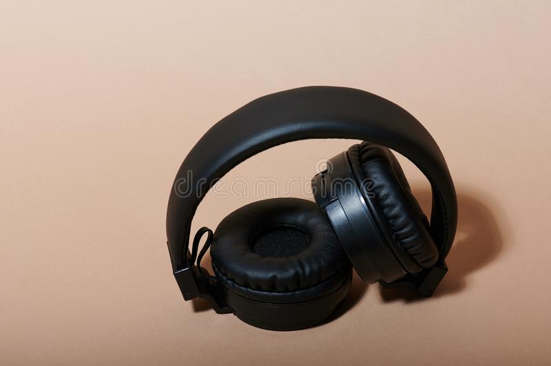 Folded black headphones. Folded black wireless headphones on beige color background royalty free stock images
