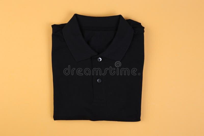 Folded black polo shirt on pastel background. Folded black polo shirt on orange pastel background stock images