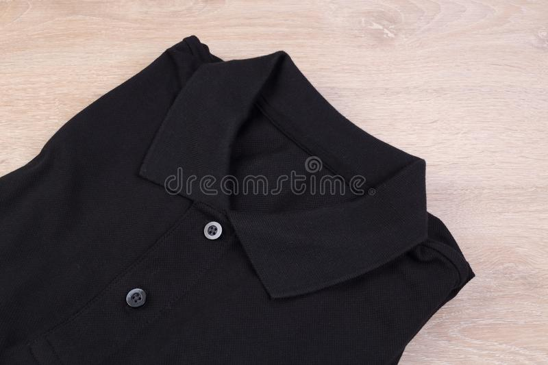 Folded black polo shirt. On wooden background stock images