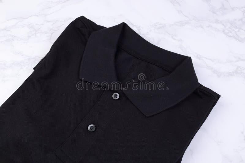 Folded black shirt polo on marble background. Folded black shirt polo on white marble background royalty free stock images