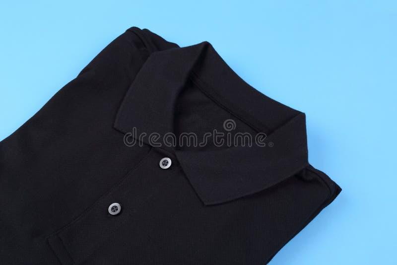 Folded black shirt polo on pastel background. Folded black shirt polo on blue pastel background royalty free stock photos
