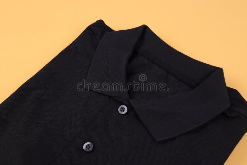 Folded black shirt polo on pastel background. Folded black shirt polo on orange pastel background royalty free stock photography