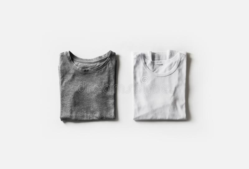 Folded blank t-shirts. Folded blank gray and white t-shirts on white paper background. Tshirt template for your design. Flat lay stock photography