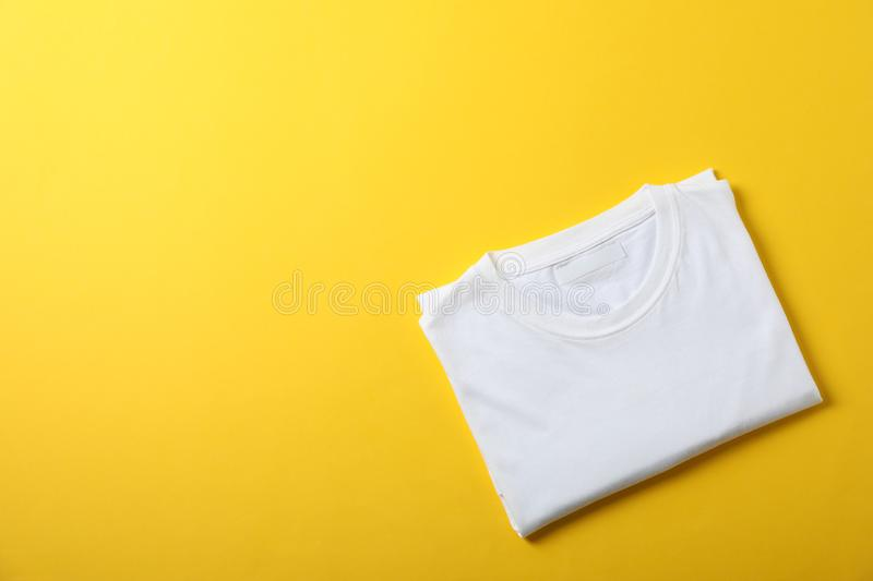 Folded blank white t-shirt on yellow background royalty free stock images