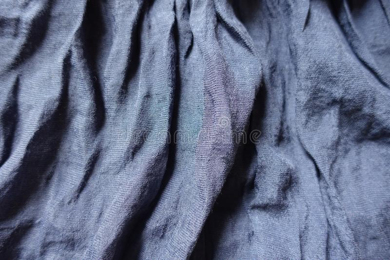 Folded blue cotton and polyester fabric. Folded thin blue cotton and polyester fabric stock images