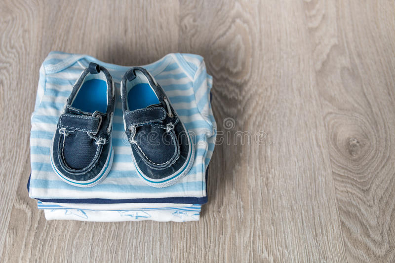 Folded blue and white bodysuit with shoes on it grey wooden background. diaper for newborn boy. Stack of infant clothing. Child o. Folded blue and white bodysuit stock photography