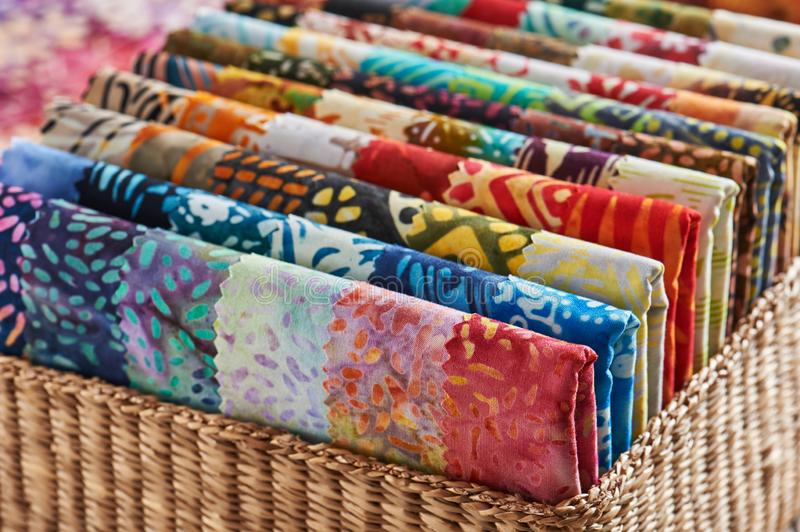 Folded bright pieces of quilting batik fabrics in a basket, macr. O royalty free stock photos