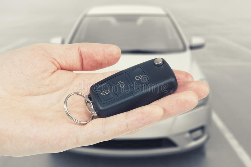 Folded car keys on a palm of a man with car on background. Folded car keys on a palm with car on background royalty free stock photography