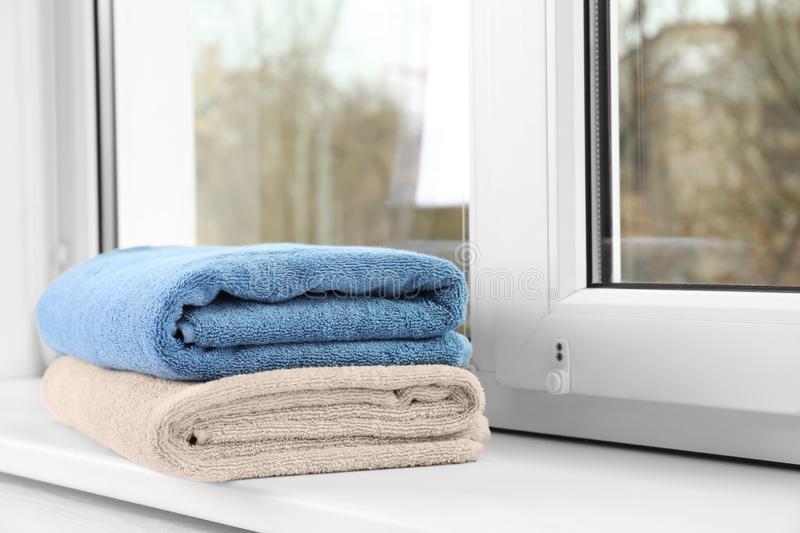 Folded clean towels on window sill. Space for text royalty free stock photography