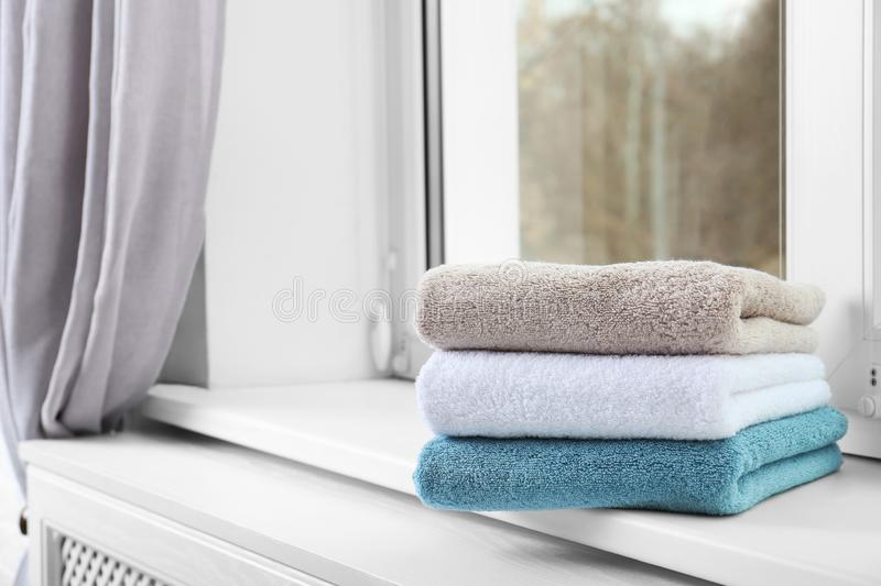Folded clean towels on window sill. Space for text stock images