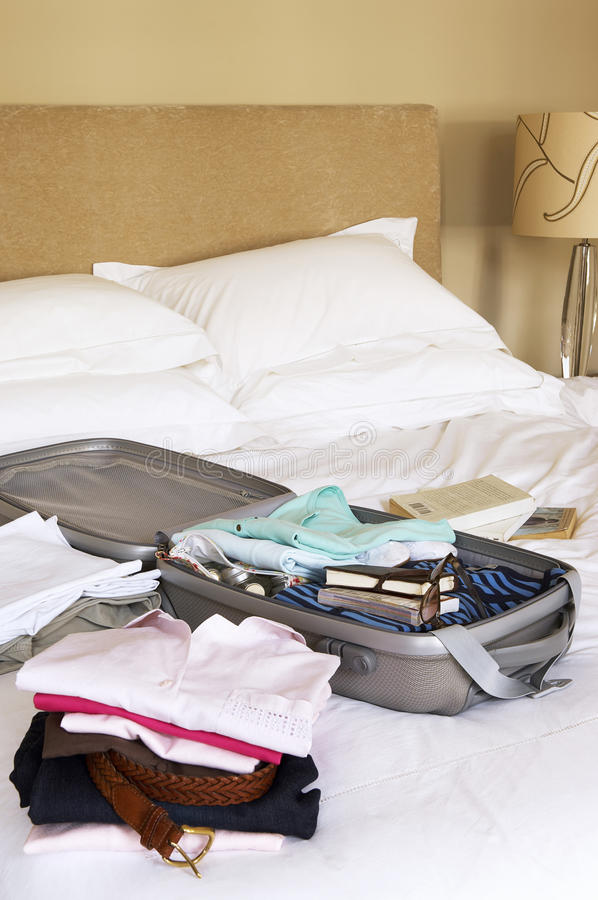 Folded Clothes And Packed Suitcase On Bed. Closeup of stacks of folded clothes and packed suitcase on bed royalty free stock image