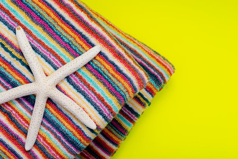 Folded Colorful Striped Organic Cotton Beach Towels decorated with White Finger Starfish on bright yellow stock photography