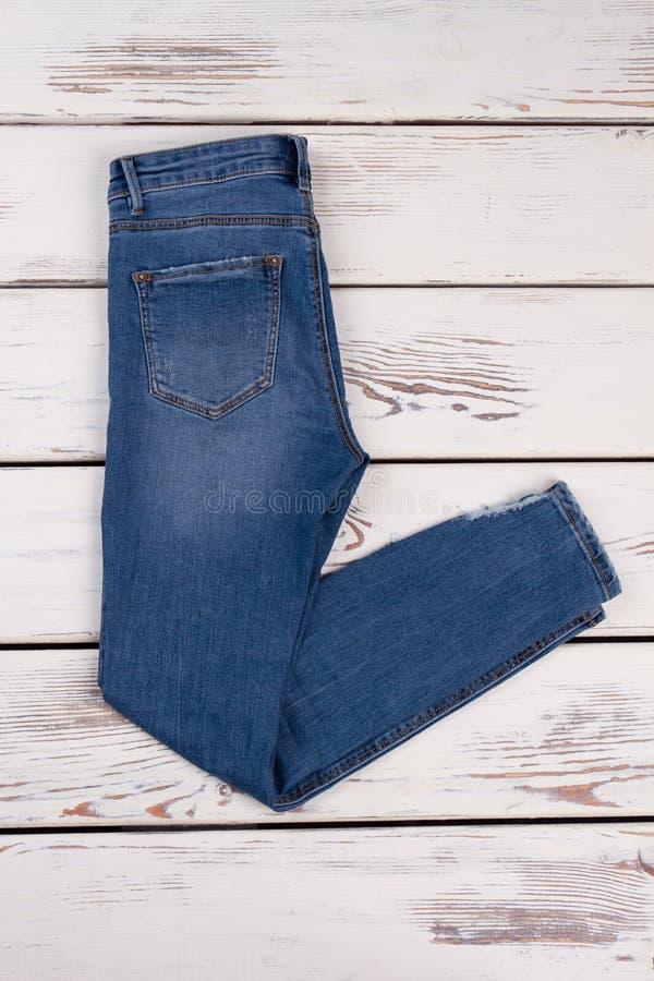 Folded denim pants on showcase. Folded denim pants on wooden showcase at the shop. Season shopping, discount for last items stock photo
