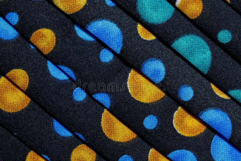 Folded fabric with red, blue, pink, gold and green dots / circles. Folded black cotton fabric with red, blue, pink, gold and green dots / circles to make an royalty free stock photo