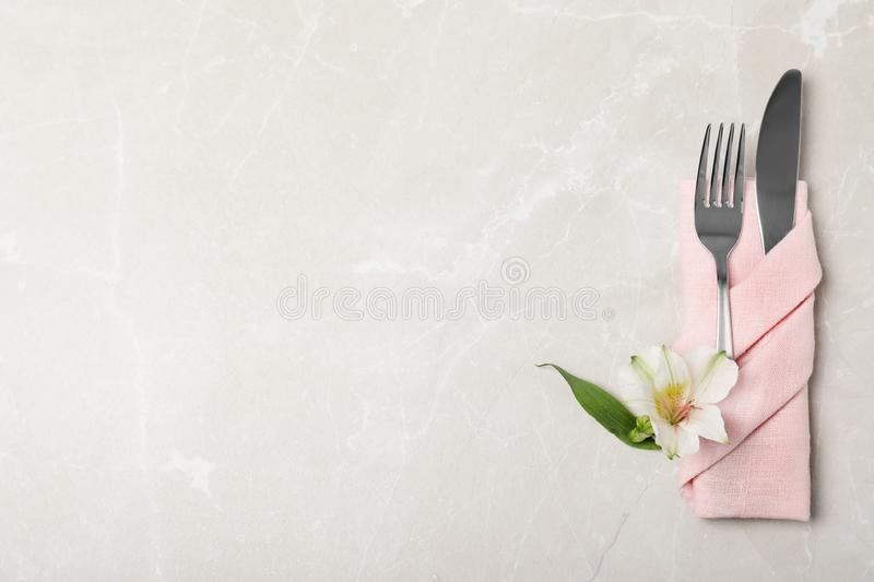 Folded napkin with fork, knife and flower on table, top view royalty free stock photos