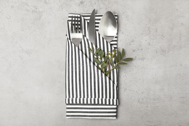 Folded napkin with fork, spoon and knife on grey background royalty free stock photo