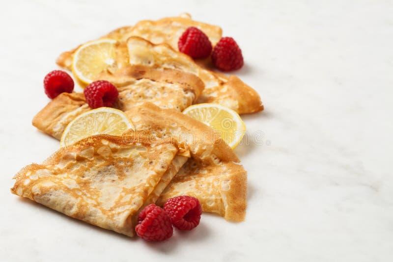 Folded pancakes on white marble background royalty free stock photos