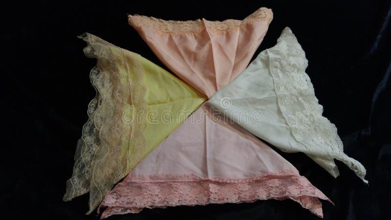 4 Folded pastel vintage lacy handkerchiefs. This is a lovely bunch of folded pastel vintage lace and cotton women& x27;s handkerchiefs . It is set on a black stock photo