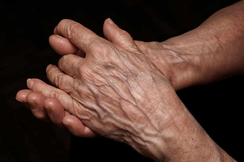 Folded senior woman wrinkled hands close up. Old age, age problems, poverty and loneliness theme royalty free stock image