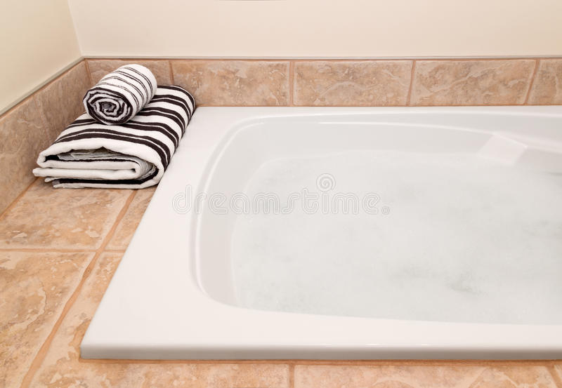 Folded Striped Towels And Bath With Foam Stock Photos