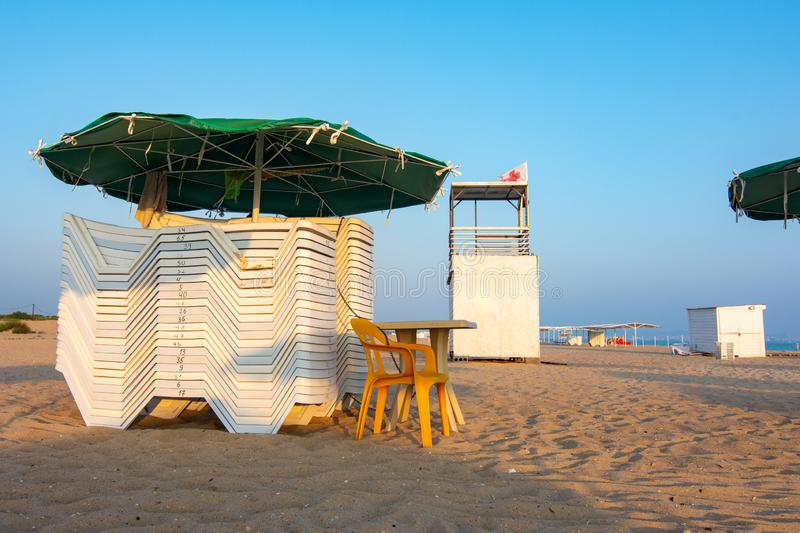 Folded sun loungers and an empty lifeguard post on a deserted sandy beach. Folded sun loungers and an empty lifeguard post on a deserted sandy  beach royalty free stock image