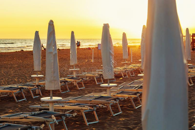 Folded sun loungers and umbrellas on an empty beach in the evening stock photos