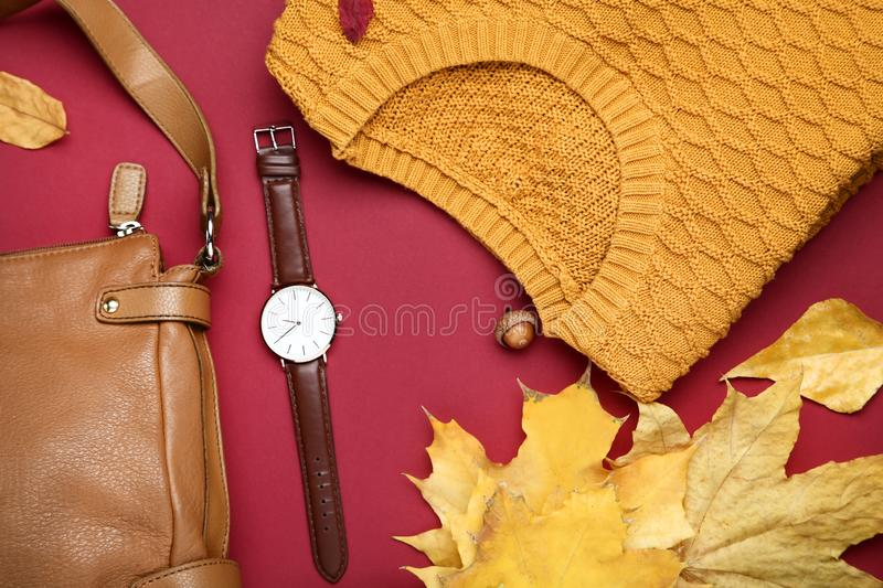 Sweater with leather bag, wrist watch. Folded sweater with leather bag, wrist watch and autumn leafs on red background royalty free stock photography