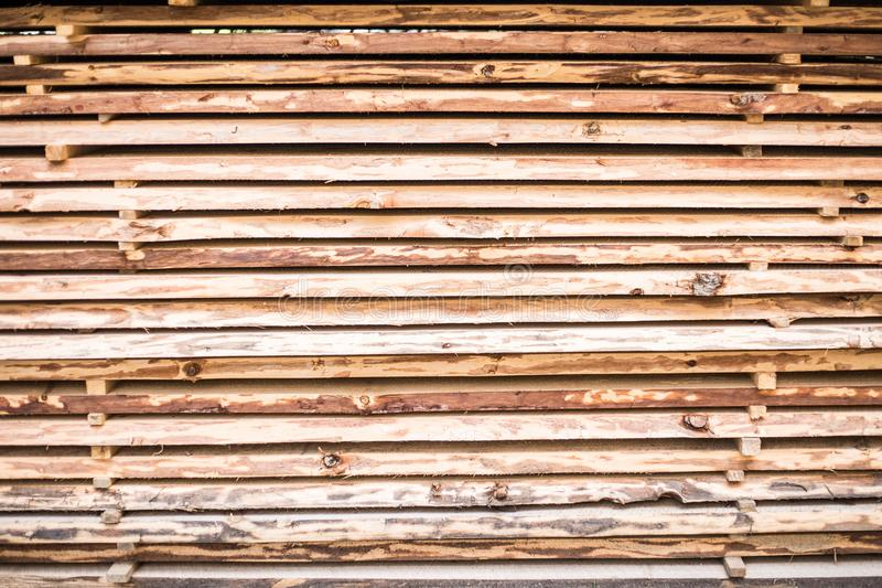 Folded in wooden piled beige beech boards. Background of uneven bars in sawmill stock image