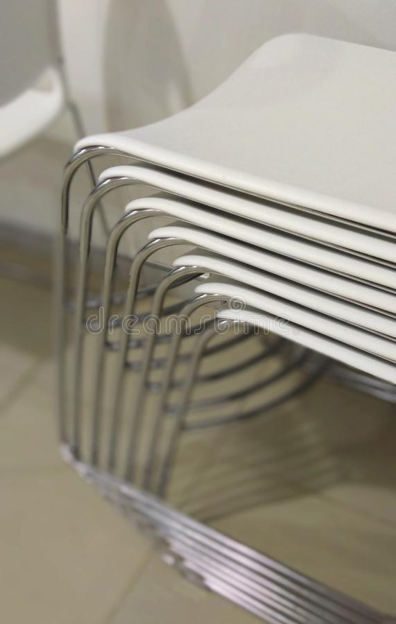 A folder of white chairs. A folder of white chairs in a dinning hall for persons stock photo