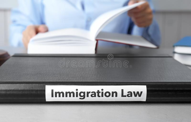 Folder with words IMMIGRATION LAW. And blurred person on background royalty free stock images