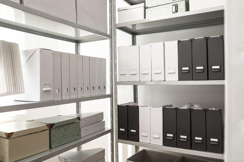 Folders and boxes with documents on shelves. In archive stock photo