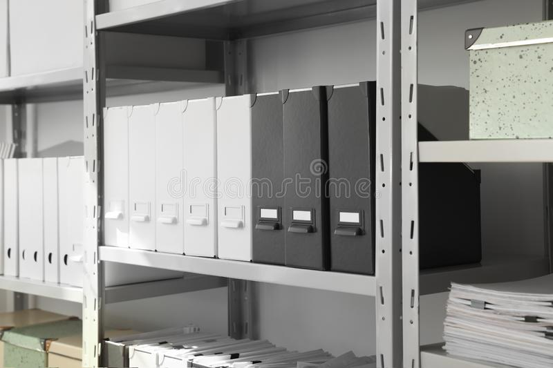 Folders and boxes with documents on shelves. In archive stock images