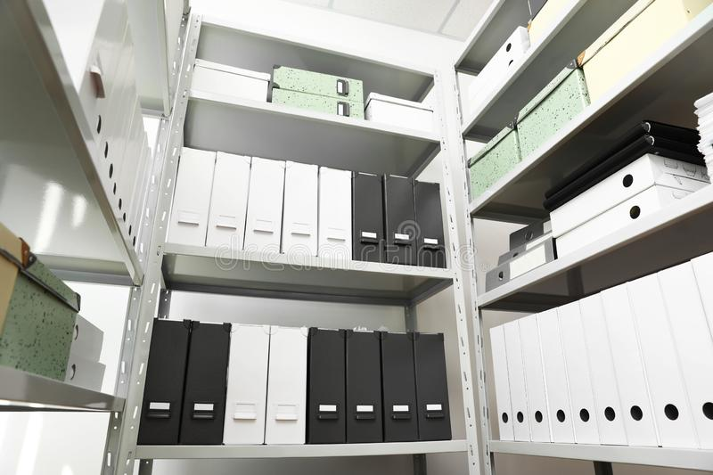 Folders and boxes with documents on shelves in archive. Low angle view stock photos