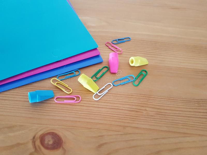 Folders and paper clips on a wooden background. Folders and paper clips laying on a wooden table, School supplies, Office supply, Back to school royalty free stock photos