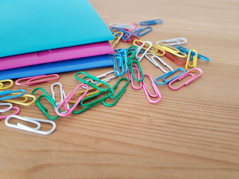 Folders and paper clips on a wooden background. Folders and paper clips laying on a wooden table, School supplies, Office supply, Back to school stock images