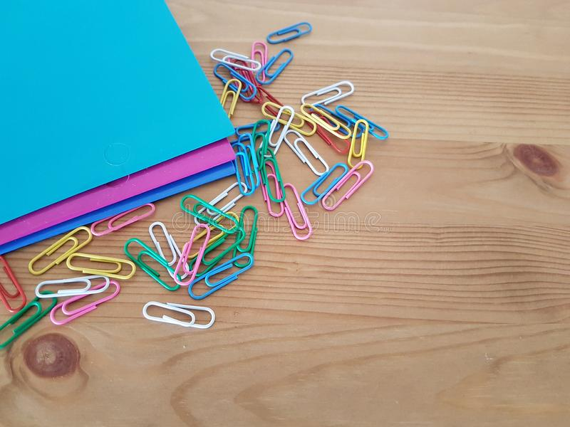 Folders and paper clips on a wooden background. Folders and paper clips laying on a wooden table, School supplies, Office supply, Back to school royalty free stock images