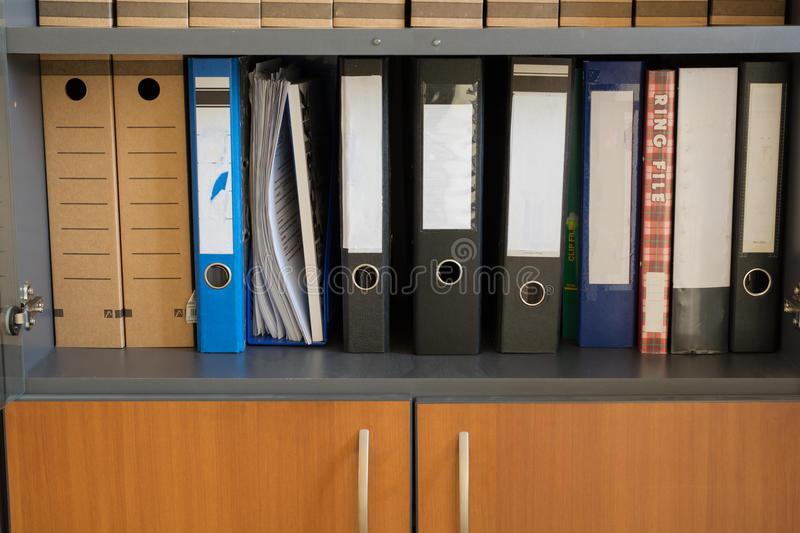 Folders in a row. Different folders on the shelf office cabinet royalty free stock photo