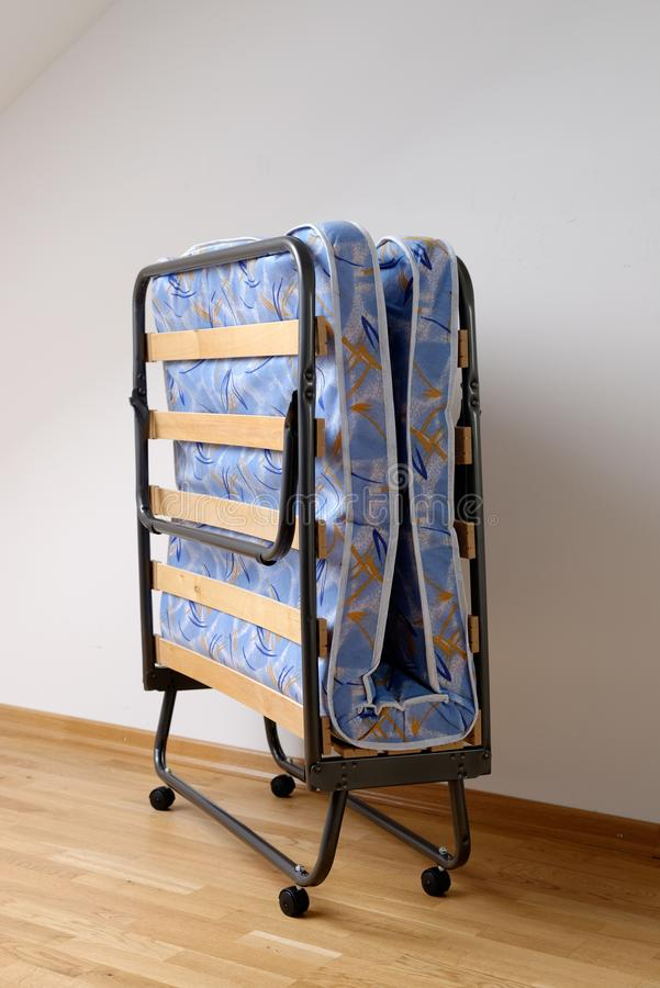 A folding bed. In front of a white wall an a blue mattress stock image