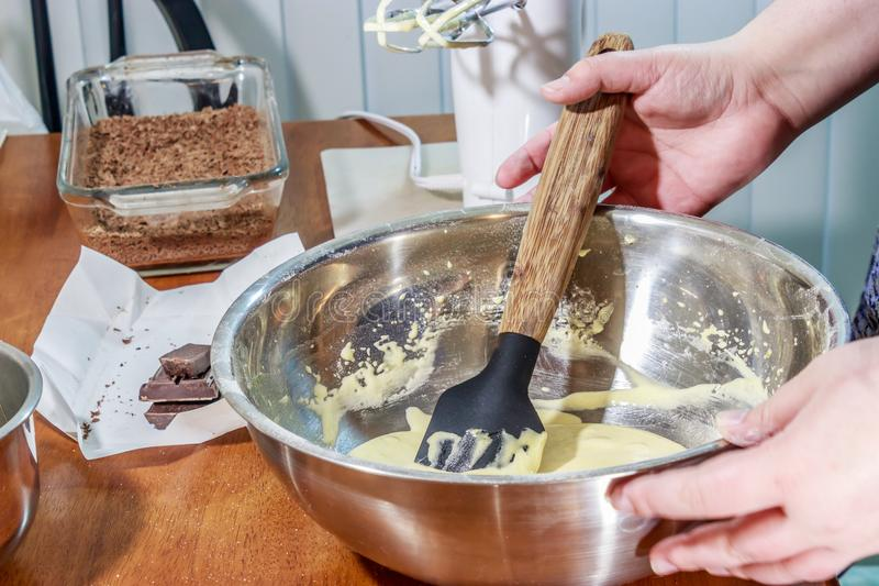 Folding cake batter together with shaved chocolate in background royalty free stock photo