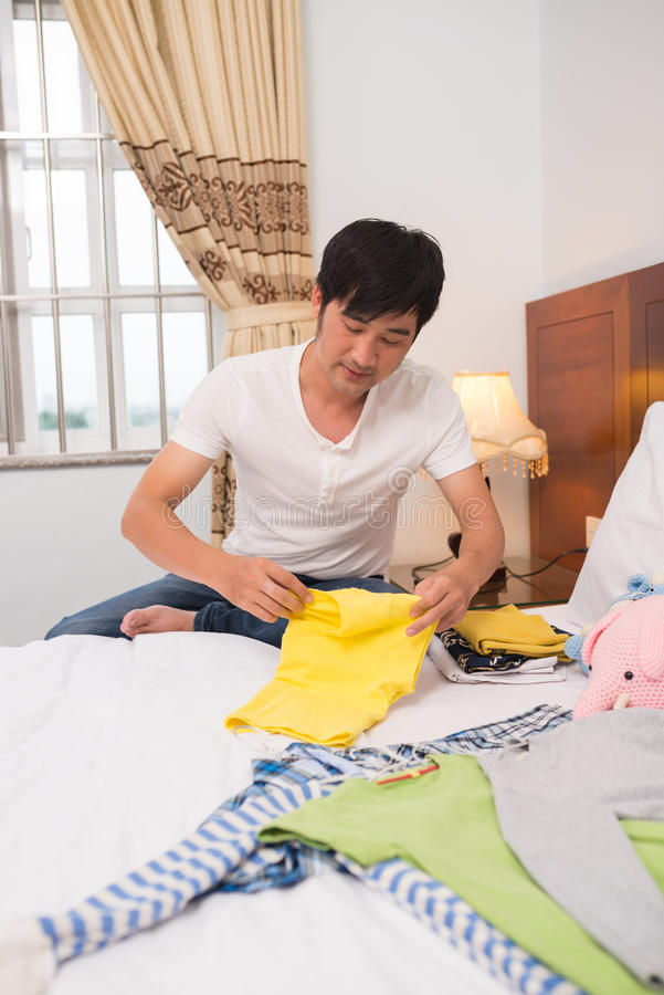 Folding clothes. Caring young dad folding clothes of his child stock photos