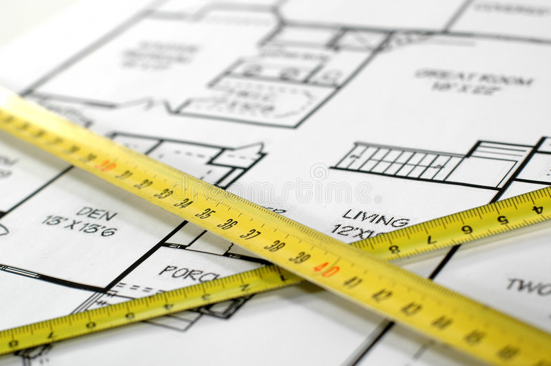 Folding rules and house architectural plan royalty free stock photo