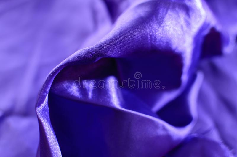 Folds of a violet fabric. The folds of the fabric form soft waves on the bed
